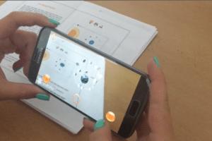 Ein Smartphone, das per App Animationen über einem Schulbuch darstellt